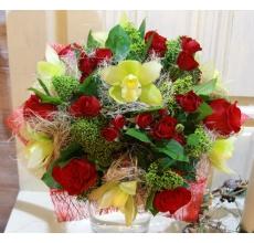 Букет из фисташковых орхидей, красных роз, красных кустовых роз, скиммии, зелени в натуральной упаковке из сизаля с лентами.