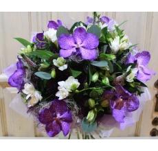 Букет из фиолетовой орхидеи ванды, вероники, белой фрезии, альстромерии, зелени в натуральной упаковке с лентами.