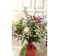 Высокий праздничный летний букет из дельфиниума, роз, гиперикума, матрикарии, альстромерии на флористическом каркасе с атласной лентой.