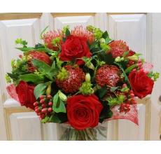 Букет из красных роз, левкоспермума, гиперикума, альстромерии, яркой зелени буплерума в натуральной упаковке с лентами