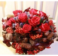 Большой букет из красных роз, листьев дуба, ирингиума, рябины на каркасе из шишек и ягод.