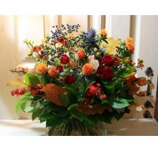 Открытый пышный осенний букет. Состав: ирингиум, картамус, красная кустовая роза, эуфорбия, калина, хелениум, листья дуба, зелень с широкой флористической лентой.