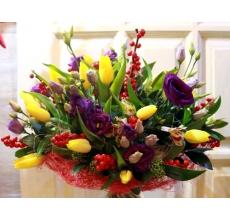 Букет из желтых тюльпанов, илекса, эустомы, альстромерии, скиммии, зелени с натуральной упаковке из сизаля с лентами.