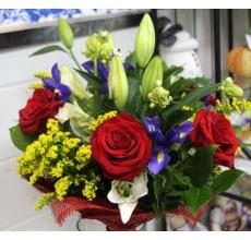 Букет из белой лилии, 5 красных роз, орнитогалума, ирисов, солидаго, зелени в натуральной упаковке из сизаля с лентами