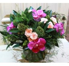 Букет из розовой орхидеи ванды, персиковой кустовой розы, скимии, аспарагуса и другой экзотической зелени без упаковки с лентами.