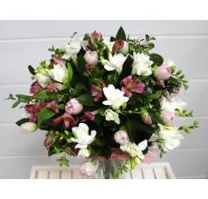 Букет из нежной белой фрезии, альстромерии, тюльпанов, зелени без упаковки с атласными лентами.